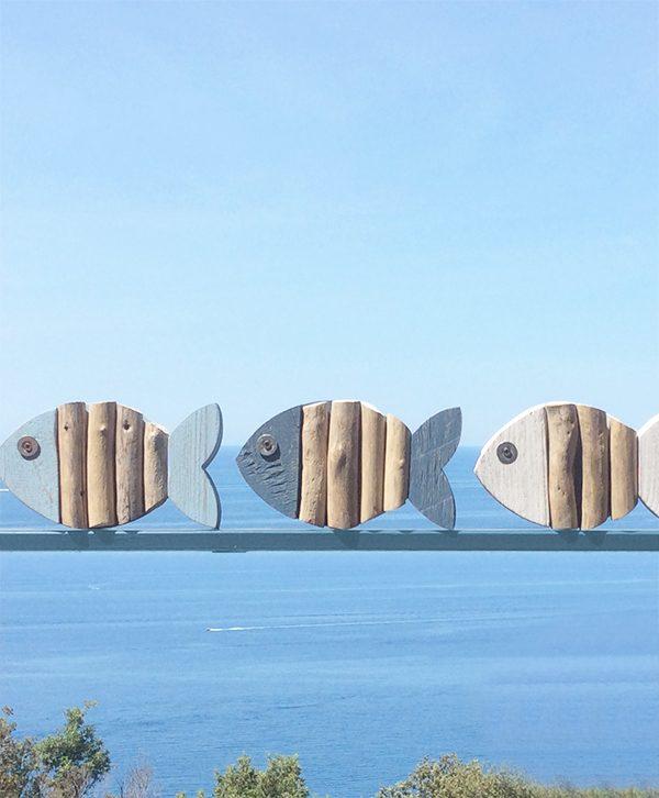 Pesci in legno con rami portati dal mare
