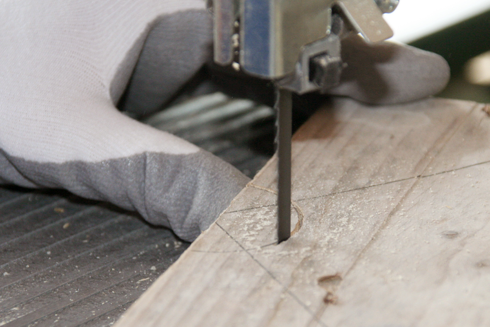 Taglio a mano di un cerchio su assi di legno di recupero