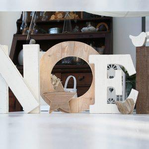 scritta noel in legno con stella e uccellino per la casa di natale