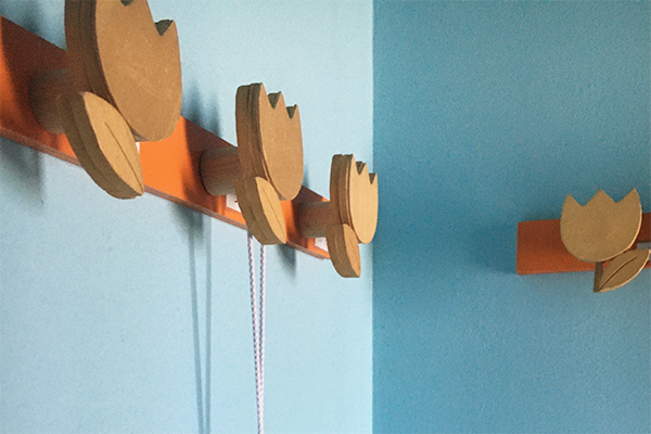 Progetto e realizzazione di una fascia decorativa con appendiabiti in un asilo nido